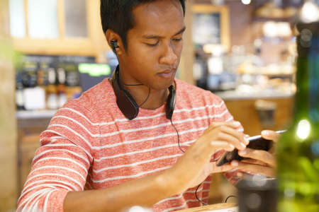 websurfing: Man in coffee shop websurfing on smartphone Stock Photo