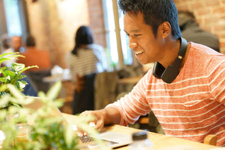 websurfing: Young man sitting in restaurant websurfing on tablet