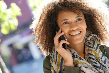 Smiling mixed raced girl talking on smartphone in the street Stock Photo
