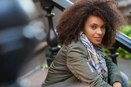 Trendy mixed raced girl sitting on NYC brick house stairs