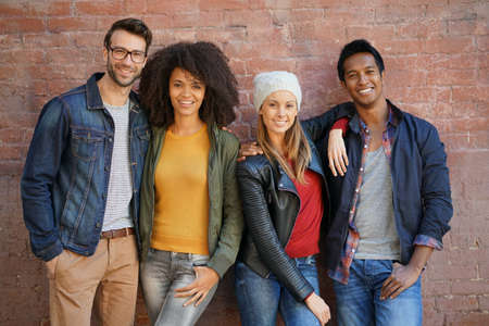 Trendy people standing in front of brick wall Stock Photo