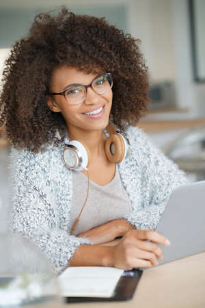 Mixed-race woman working from home on laptop computer