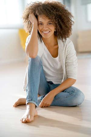 mujer alegre: Alegre mujer de raza mixta sentado en el piso de madera