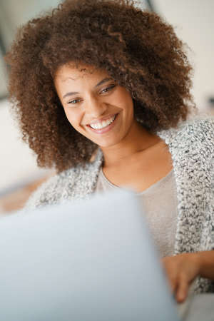 websurfing: Beautiful woman at home websurfing with laptop computer Stock Photo