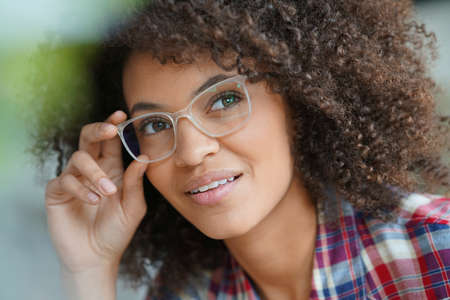 specs: Attractive mixed race woman with eyeglasses relaxing in armchair