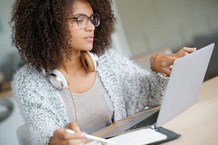 trabajando en casa: Mujer de raza mixta trabajando desde casa en la computadora portátil