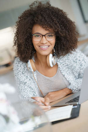 websurfing: Mixed-race woman working from home on laptop computer