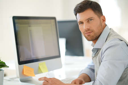 guys: Handsome businessman working on desktop computer in office
