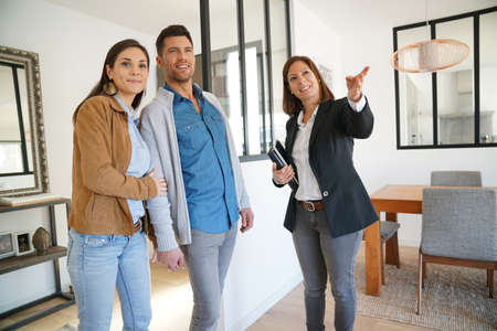 Couple with real-estate agent visiting house for sale Foto de archivo