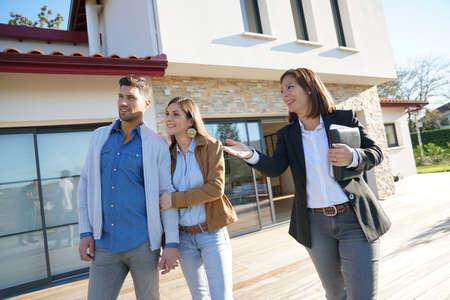 Pares con el agente de bienes raíces visitando la casa en venta Foto de archivo - 67117508