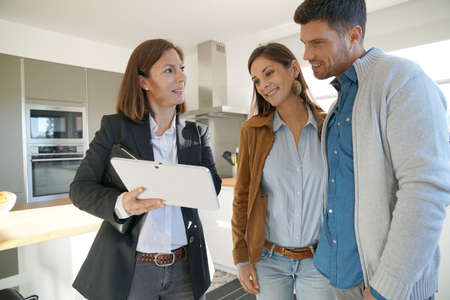 Couple with real-estate agent visiting house for sale 스톡 콘텐츠