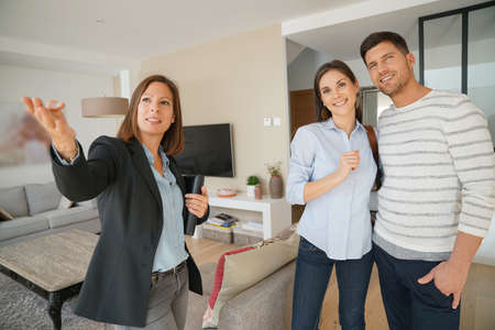 house sale: Couple with real-estate agent visiting house for sale Stock Photo