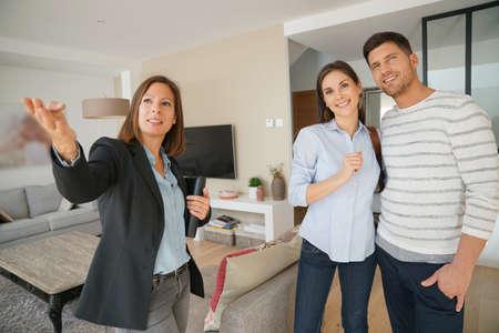 vendedor: Pares con el agente de bienes raíces visitando la casa en venta