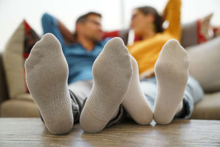 men socks: Closeup of couples feet laid on table Stock Photo