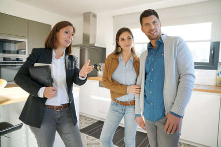 home sale: Couple with real-estate agent visiting house for sale Stock Photo