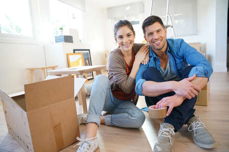 Cheerful couple moving in new home, surrounded by cardboards