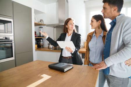 Pares con el agente de bienes raíces visitando la casa en venta
