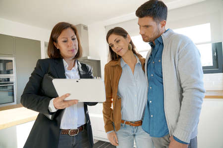 Couple with real-estate agent visiting house for sale Banco de Imagens