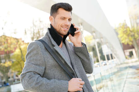 Handsome businessman talking on phone outside Stock Photo