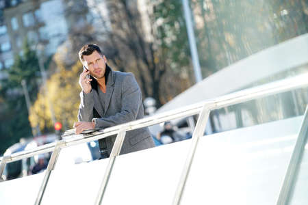 View of businessman talking on phone, from bridge