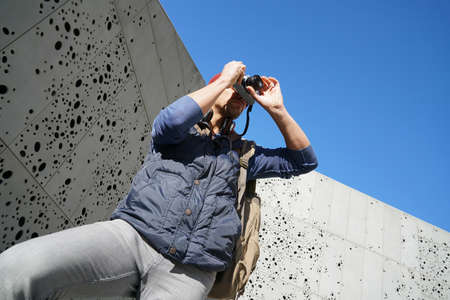 Man standing by concrete modern wall, taking pictures