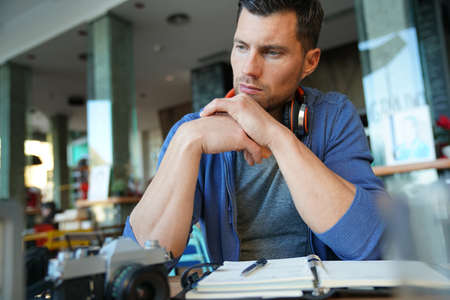 Man sitting in restaurant writing notes on agenda Stock Photo