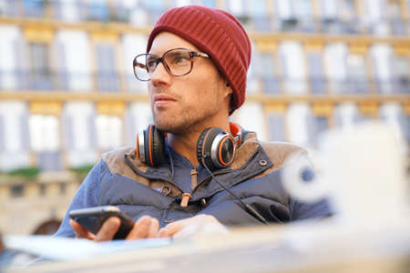 30 years old man: Hipster guy relaxing at caf? terrace, using smartphone