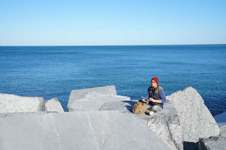 Young reporter connected on tablet by the ocean Stock Photo