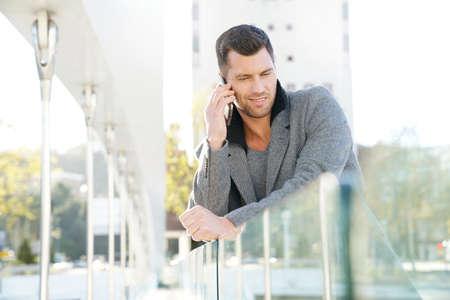 Handsome businessman talking on phone outside