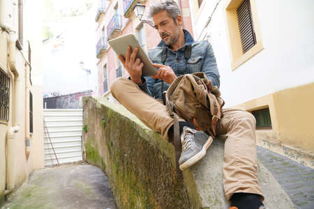 Tourist in historical town connected on digital tablet