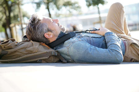 Traveller laying on concrete bench in town