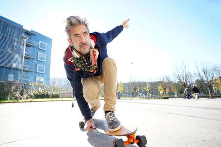 Oudere man skateboarden in de straat Stockfoto