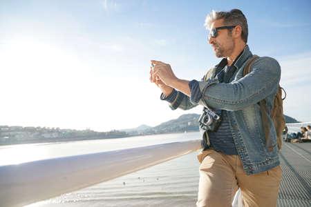 Man standing by the sea using smartphone, winter season Stock Photo