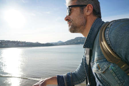 globetrotter: Man standing by the sea using smartphone, winter season Stock Photo