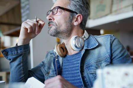 Mature man in coffee shop writing notes on agenda Stock Photo
