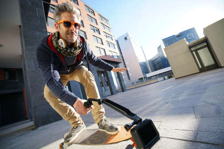 Mature man skateboarding in urban environment, filming himself Imagens