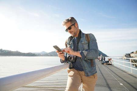 persona viajando: El hombre de pie junto al mar utilizando teléfono inteligente, la temporada de invierno
