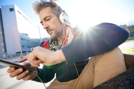 Skateboarder listening to music with smartphone and headphones