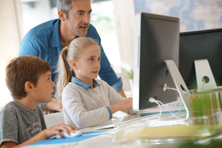 3 persons: Teacher with school kids in computer laboratory