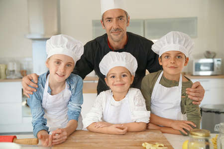 adult learners: Retrato de pastelero felices juntos con los niños en clase de cocina