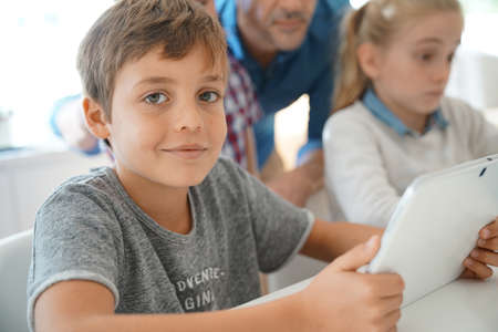 schoolboy: Portrait of schoolboy in classroom learning with digital tablet