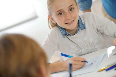 niños estudiando: Retrato de niña de la escuela a tomar notas en clase