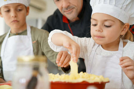 Pastry chef watching kids preparing apple pie