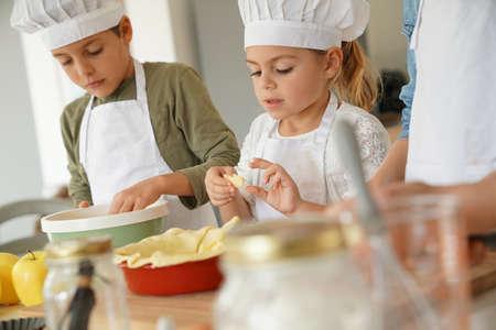 niños cocinando: Los niños en el taller clase de cocina que preparan el pastel de manzana Foto de archivo