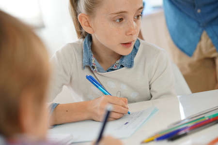 elementary schools: Portrait of school girl taking notes in class Stock Photo