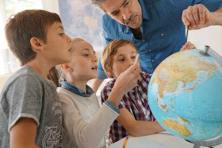 지구를보고있는 지리 학급의 아이들과 함께 사는 선생님 스톡 콘텐츠