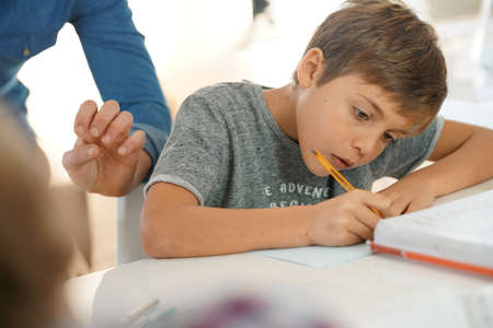 elementary schools: Portrait of pupil in school class taking notes during writing lesson Stock Photo