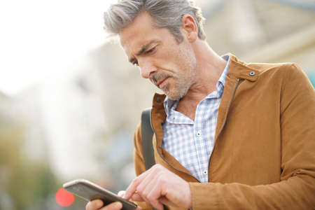 Mature man in town sending message with smartphone