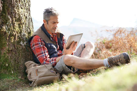 Hiker relaxing by tree looking at map and using tablet