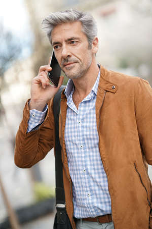 Mature handsome man in the street talking on phone